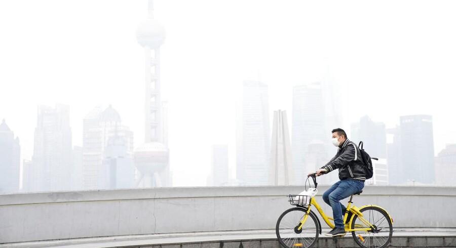 En ung mand med ansigtsmaske cykler forbi Shanghais finansdistrikt Pudong på en smogfyldt dag i november.