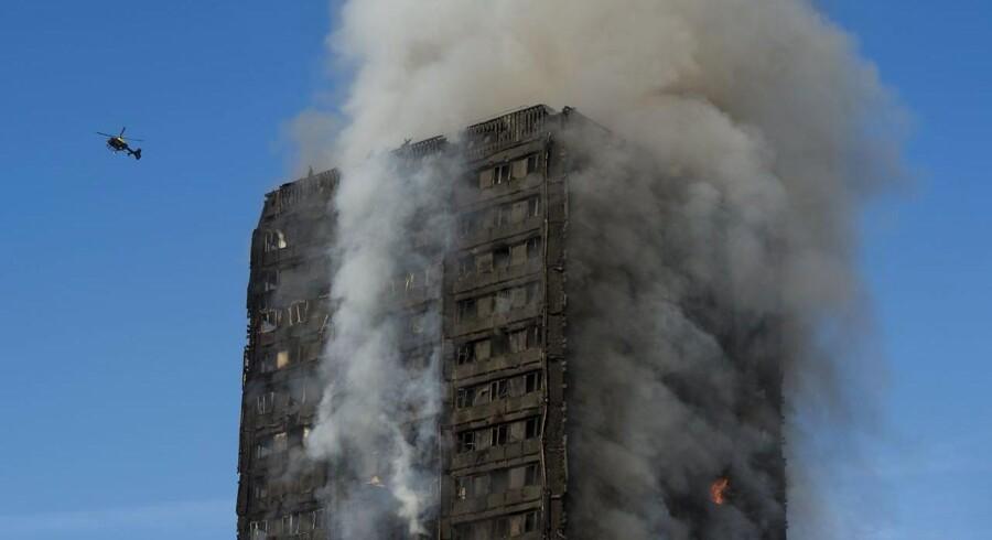 Røg stiger op fra bygningen Grenfell Tower i North Kensington i London 14. juni 2017. 40 brandingeniører og 200 brandmænd har kæmpet for at evakuere beboere og slukke branden. EPA/WILL OLIVER