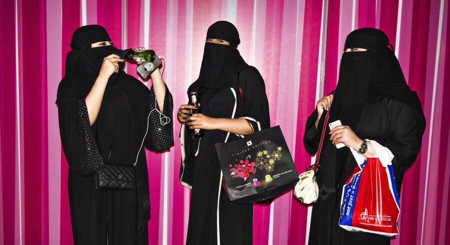 - -Årets billeder 2016- - Pigerne Hanoof Adel på 22 år, Jumanah Aziz 21 og Amjad Alsihaibani 19 står foran en Victorias Secret lingeributik og drikker alkoholfri øl, mens de nyder søndagsfriheden. Saudi-Arabien er kendt for at være landet, hvor kvinder har meget få rettigheder. For eksempel er det ikke tilladt for kvinder at køre bil og alle kvinder, også vestlige på besøg, skal bære abaya. (Arkivfoto) (Foto: Mathias Løvgreen Bojesen/Scanpix 2016)