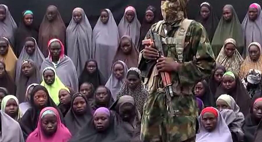 Boko Haram har søndag offentliggjort en video, der angiveligt viser de kidnappede skolepiger fra Chibok. Billedet, der er taget fra videoen, viser angiveligt en af gruppens medlemmer foran de bortførte piger. Scanpix/Ho