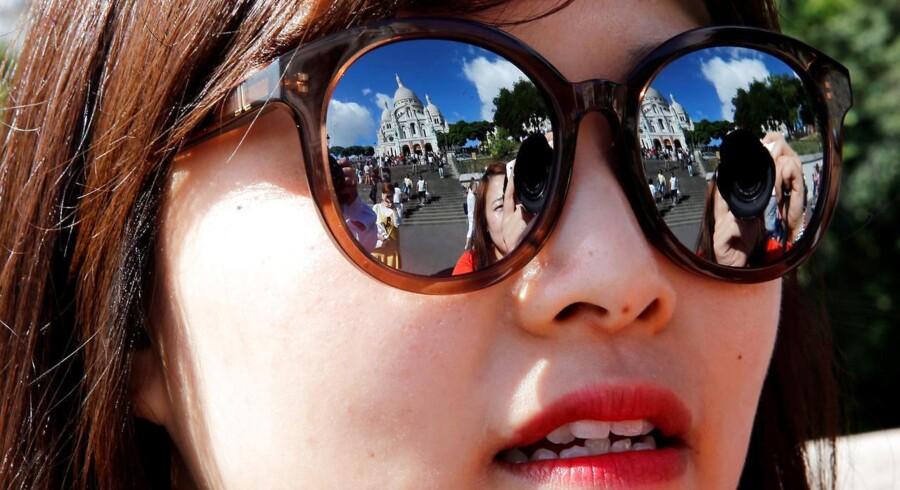 Sacre Coeur kirken i Paris reflekteres i solbrillerne på en koreansk turist.