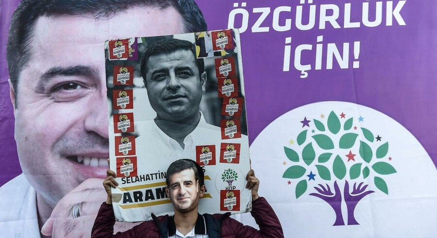 En støtte af det prokurdiske HDP-parti havde både billede af den fængslede præsidentkandidat, Selahattin Demirtas, og en Demirtas-maske med til en demonstration i Istanbul. Foto: Yasin Akgul/AFP/Ritzau