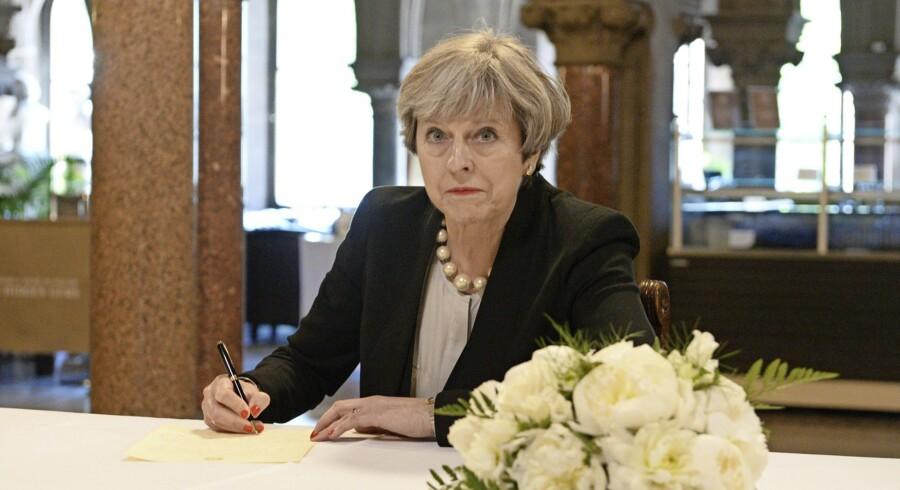 Premierminister Theresa May i færd med at skrive en hilsen til de efterladte til ofrene for terrorangrebet, tirsdag på Manchesters rådhus. Foto: Ben Birchall