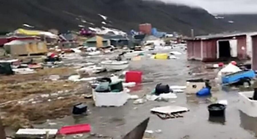 Lørdagens flodbølge menes at stamme fra et jordskred fra et fjeld. Bagefter blev flere bygninger skyllet væk, og fire personer var søndag aften fortsat savnet.