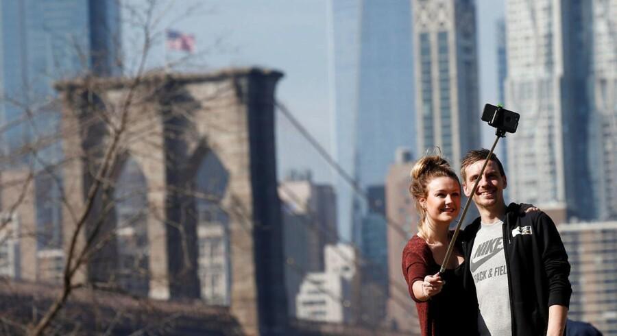 Turister nød onsdag det helt usædvanligt varme vejr i New York, her med Brooklyn Bridge i baggrunden for en selfie.