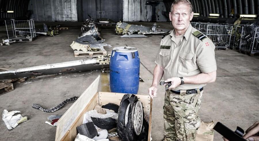 Generalmajor Stig Østergaard Nielsen med de sørgelige rester af det danske F-16-fly, der styrtede i havet ved Rømø. I trækassen er ?den lille, runde synder: Det var et eksploderet dæk, der til sidst tvang F-16-piloten til at forlade sin kostbare maskine. Foto: Michael Drost-Hansen