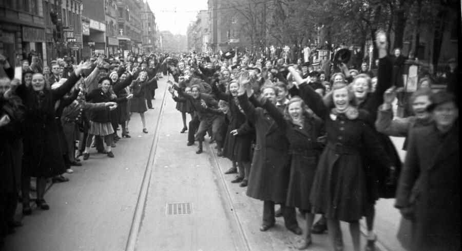 ARKIVFOTO: Danmarks Befrielse. Befrielsen fejres og her ses mange danskere der har taget opstilling langs Amagerbrogade for at få et glimt af de britiske soldater der kørte igennem København.De første allierede soldater - engelske faldskærmsjægere- landende i Kastrup lufthavn d. 5. maj og kørte i triumftog gennem København i lastbiler stillet til rådighed af frihedskæmpere.
