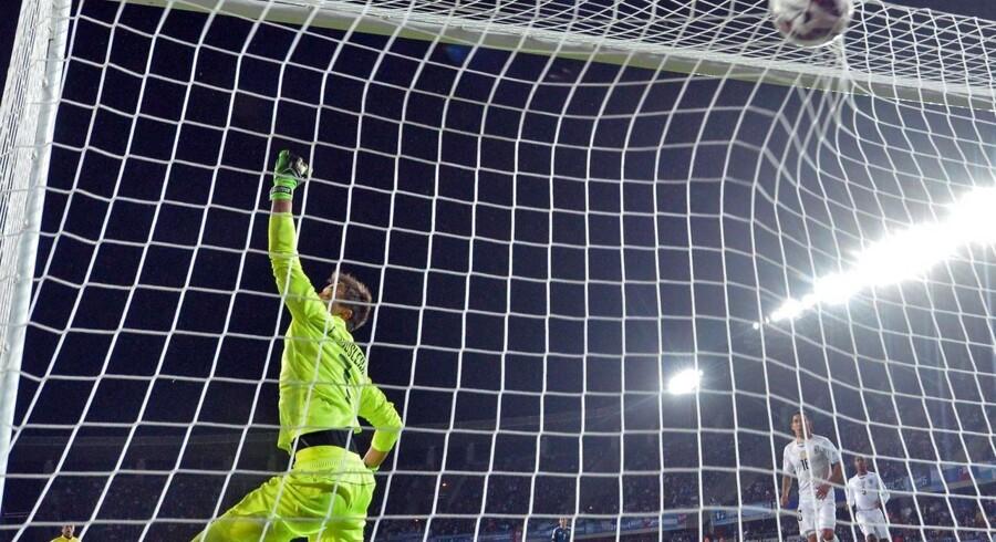 Fernando Muslera spræller forgæves efter Sergio Agueros hovedstød, der afgjorde kampen mellem de sydamerikanske rivaler, Argentina og Uruguay.