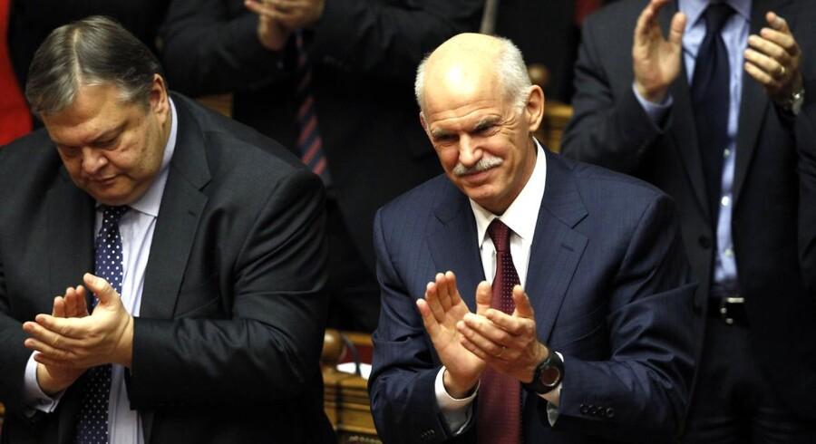 Premierminister George Papandreou og finansministerEvangelos Venizelos klapper efter at have vundet tillidsafstemningen fredag ved midnatstid.