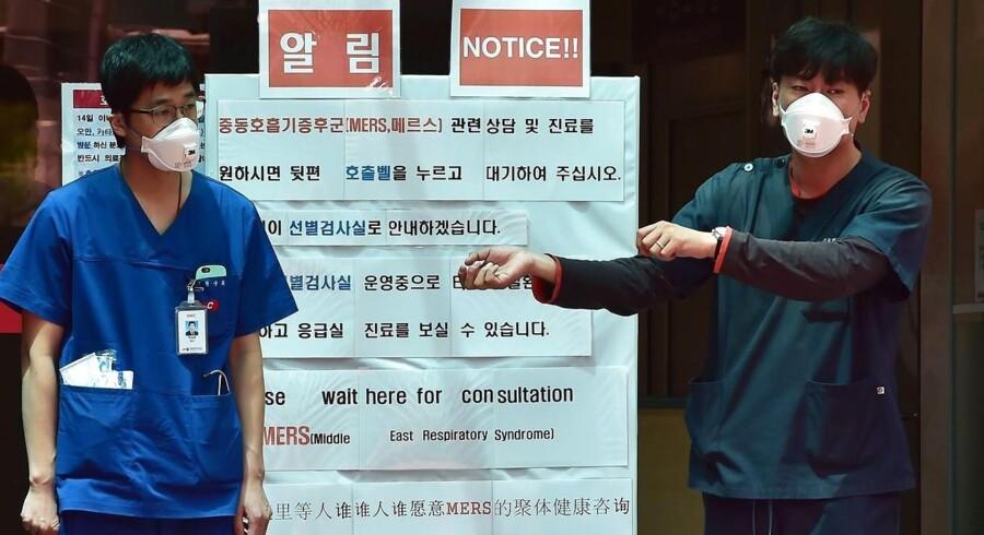Sydkoreanske hospitalsansatte bærer masker foran et informationsopslag om MERS.