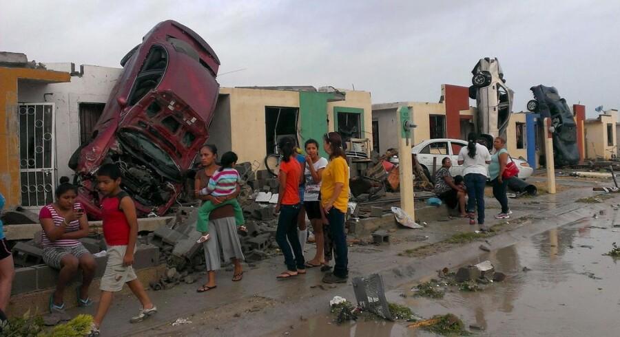 Borgere og ødelagte biler i byen Ciudad Acuna i Mexico efter en tornado ramte mandag.