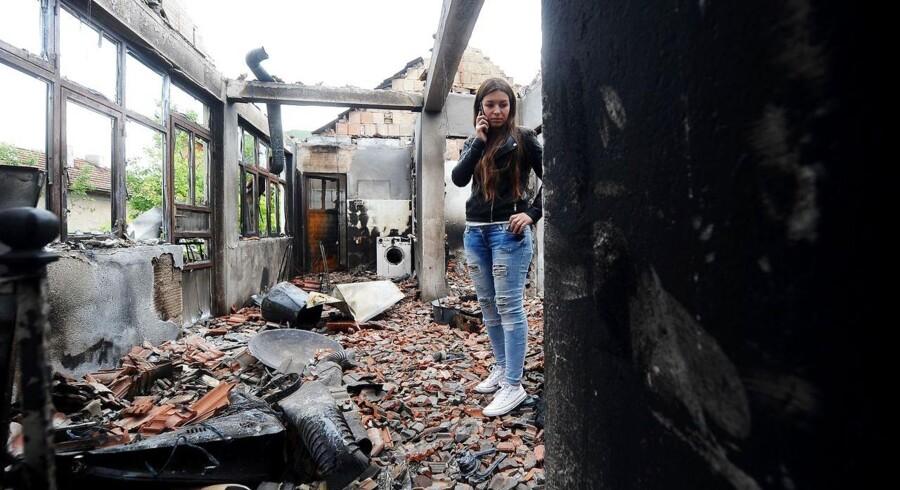 En kvinde i ruinerne af hendes hjem.