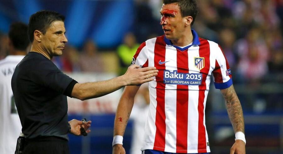 Atletico Madrids Mario Mandzukic måtte forlade banen undervejs i kampen mod Real Madrid efter en duel med Sergio Ramos.