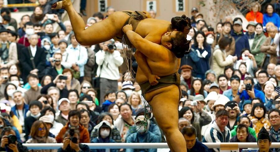 Japans traditionsrige sport kan stadig lokke tusindvis af tilskuere til. Se billederne fra dne årlige »Honozumo«-turnering i Tokyo.En bryder kaster sin modstander op i luften.