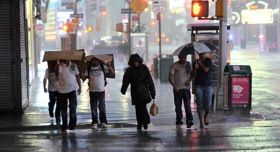 Folk prøver at beskytte sig mod regnen med både pap og paraplyer på Times Square i New York.