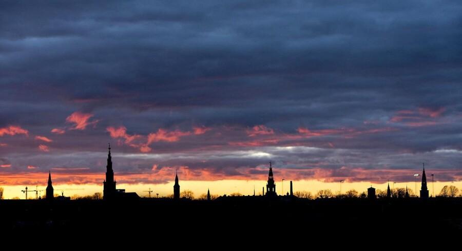 Arkiv: Solnedgang over København og byens tårne set fra Kløvermarken på Amager. Blandt andet ses Frelser Kirkes tårn, Rådhustårnet, Domkirken og tårnet på Christiansborg.