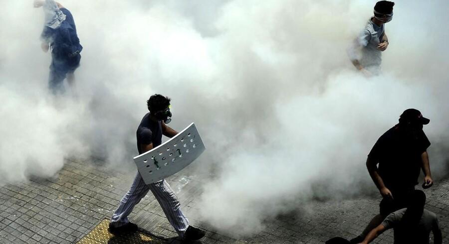 Demonstranter med gasmasker i Athen.