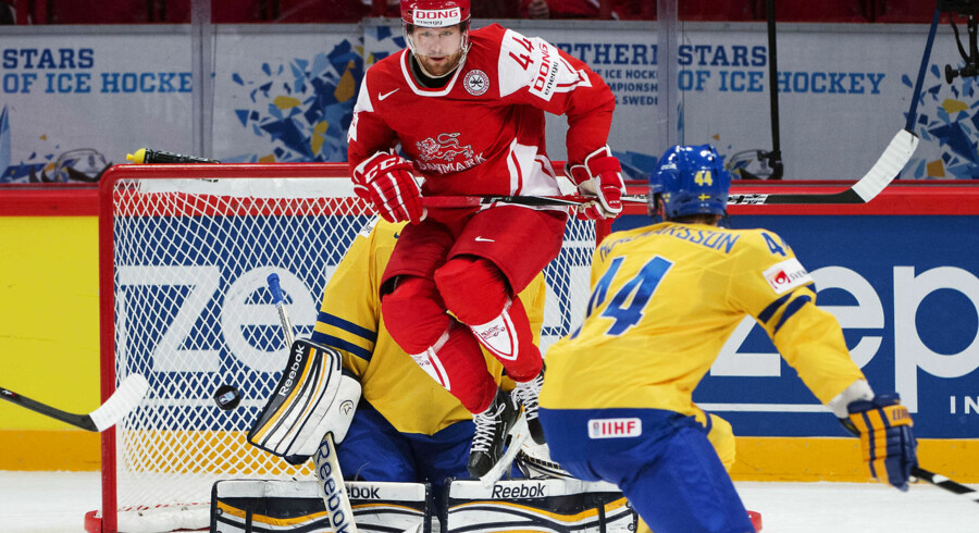 Denmark's Nichlas Hardt (Top) jumps to clear the way to his teammate Philip Larsen's (unseen) shooting against Sweden's goalkeeper during a preliminary round match at the Ice Hockey World Championships in Stockholm on May 7, 2012. Sweden won 6-4. AFP PHOTO/ JONATHAN NACKSTRAND