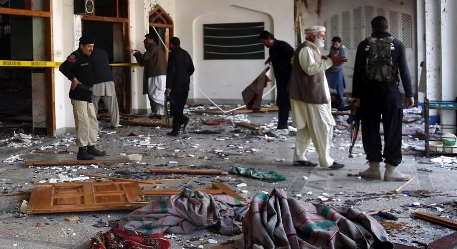 Sikkerhedsstyrker undersøger moskeen i Pesharwar efter angrebet.
