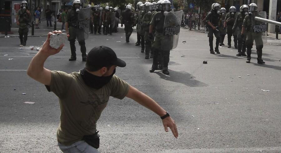 En demonstrant kaster sten mod det gærske politi foran regeringsbygningen ved Syntagma Square i går.