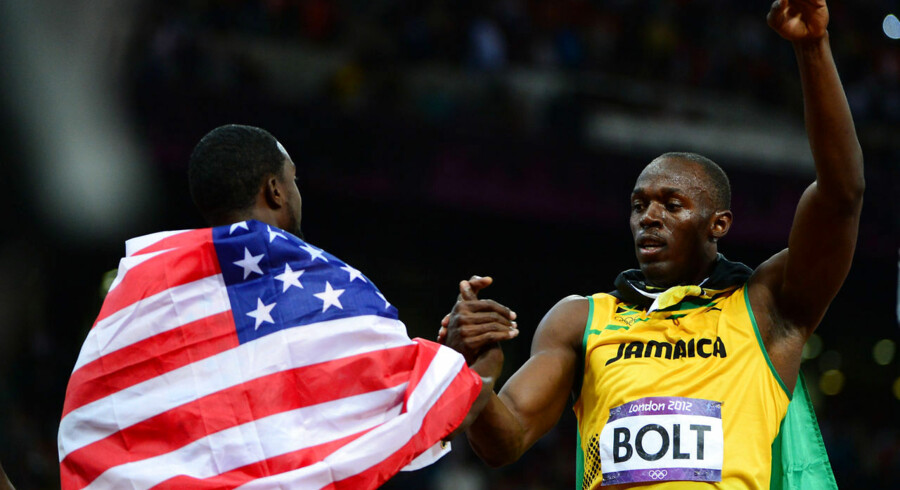 Jamaica's Usain Bolt (L) celebrates with US' Justin Gatlin after winning the men's 100m final at the athletics event during the London 2012 Olympic Games on August 5, 2012 in London. AFP PHOTO / OLIVIER MORIN