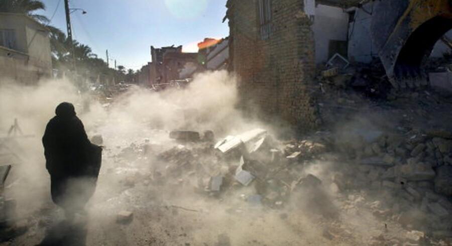 En kvinde indhyllet i støv undgik i går med nød og næppe en væltende mur fra et sammenstyrtet hus i Bam. Foto: Odd Andersen