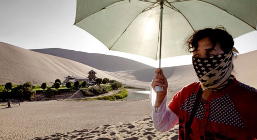 Ørkenspredning skyldes typisk klimaforandringer og menneskelige aktiviteter. På billedet ses en kvinde, der skærmer sig for den barske sol i ørkenen i det nordvestlige Kina.
