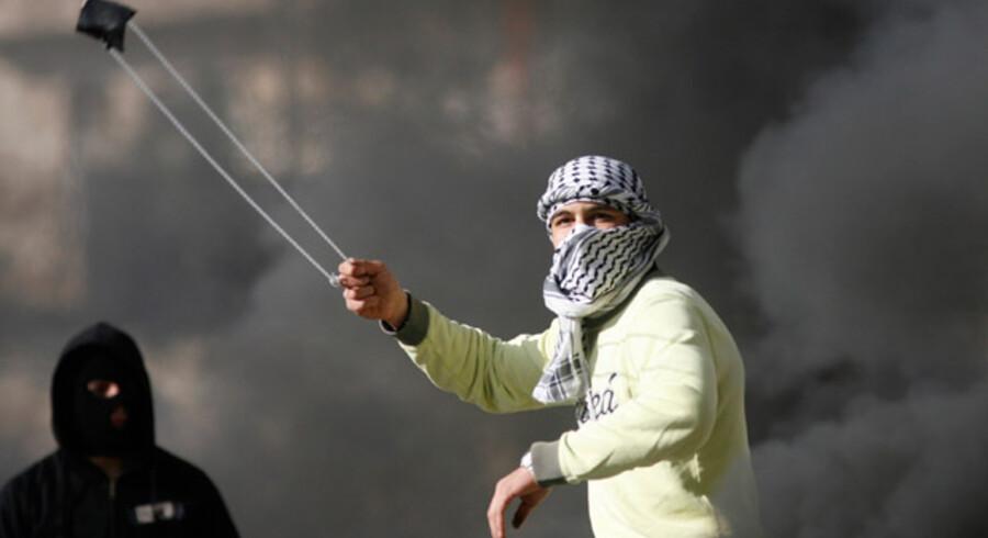 En vred demonstration slynger her sten mod politiet ved et check point i Ramallah på Vestbreden.