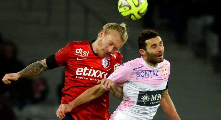 Lille's Danish defender Simon Kjaer (L) jumps for the ball with Evian's French midfielder Cedric Barbosa during the French L1 football match between Lille (LOSC) and Evian (ETGFC) on January 7, 2015 at the Pierre-Mauroy stadium in Villeneuve-d'Ascq, northern France. AFP PHOTO / DENIS CHARLET