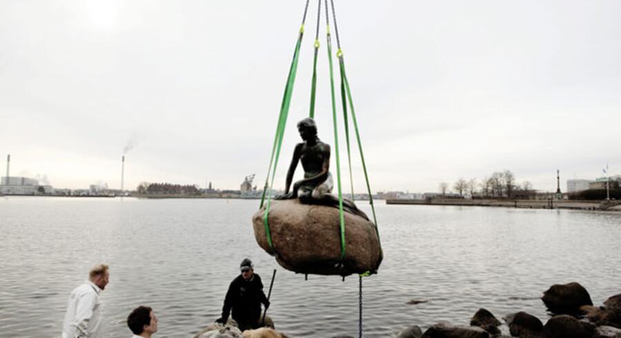 Pludselig lettede Havfruen på sin sten, mens alle folk så til.