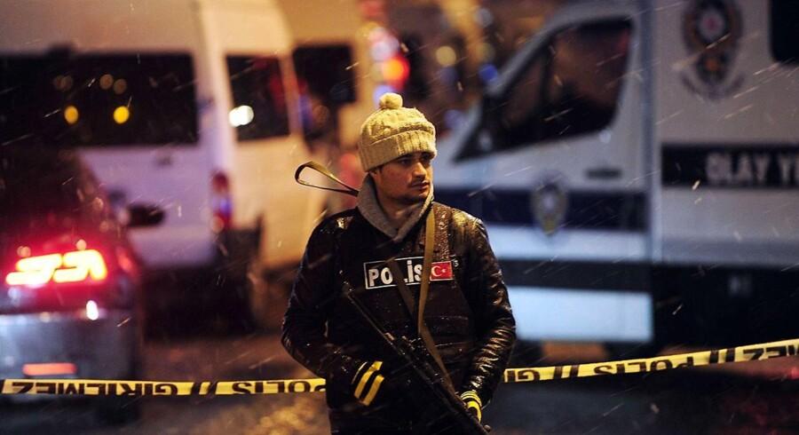 En betjent står vagt ved politistationen i Istanbul, hvor en selvmordsbomber tirsdag udløste en håndgranat.