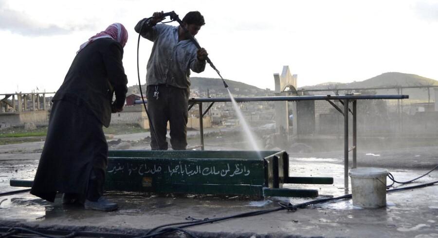En mand vasker blod af en kiste i byen Idlib.