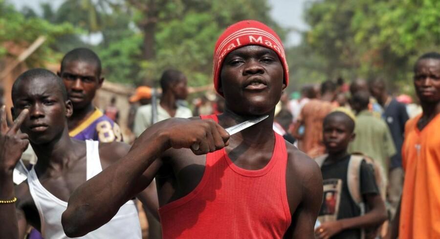 ARKIVFOTO 2014. En mand i Bangui, der holder en kniv til struben, hævder, at han leder efter muslimer, han kan skære hovedet af.