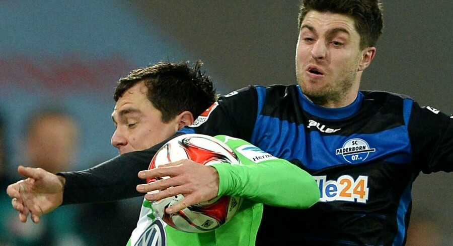 Paderborn's midfielder Moritz Stoppelkamp (R) and Wolfsburg's defender Marcel Schaefer vie for the ball during the German First division Bundesliga football match VfL Wolfsburg v SC Paderborn 07, in Wolfsburg, Germany, on December 14, 2014. AFP PHOTO / DPA / PETER STEFFEN +++++GERMANY OUT RESTRICTIONS - DFL RULES TO LIMIT THE ONLINE USAGE DURING MATCH TIME TO 15 PICTURES PER MATCH. FOR FURTHER QUERIES PLEASE CONTACT DFL DIRECTLY AT + 49 69 650050