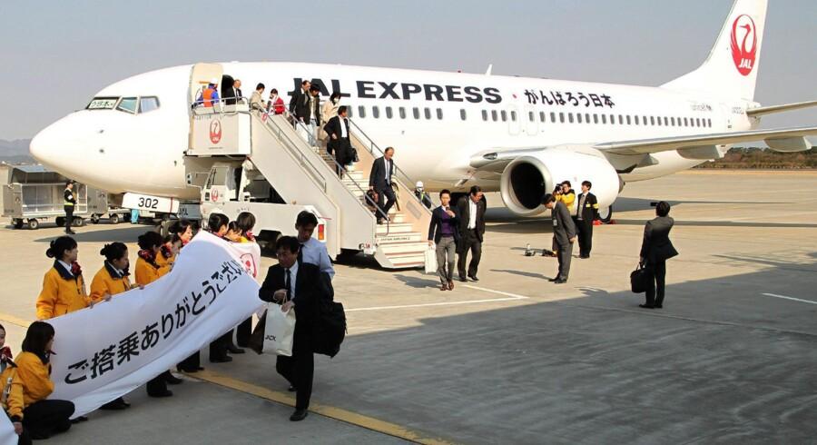 Passagererne på det første kommercielle fly til Sendai bliver modtaget af lufthavnens ansatte.