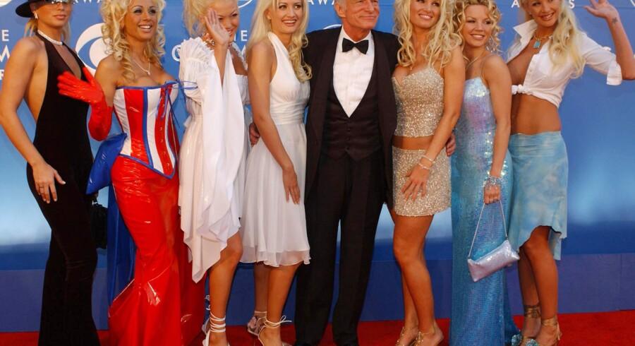 """Playboy-mogulen Hugh Hefner fylder i dag 85 år. Han har gennem hele livet sørget for masser af kvindelige bekendtskaber.Her ses en 75-årig Hugh Hefner med nogle af sine mange """"veninder"""" til Grammyuddelingen i 2002."""