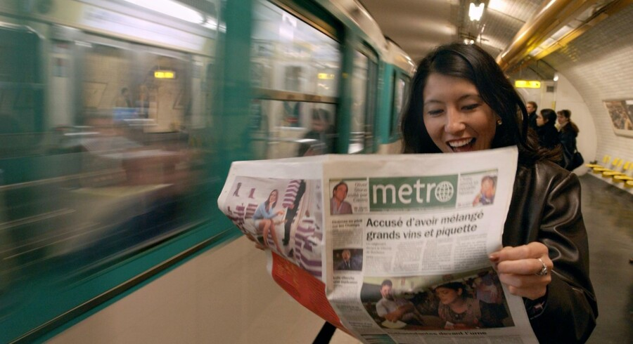 En smilende kvinde i Paris står på en perron og læser i den dangang nye gratisavis Metro, 19. februar 2002. Nu lancerer Metro International en ny branding-kampagne.