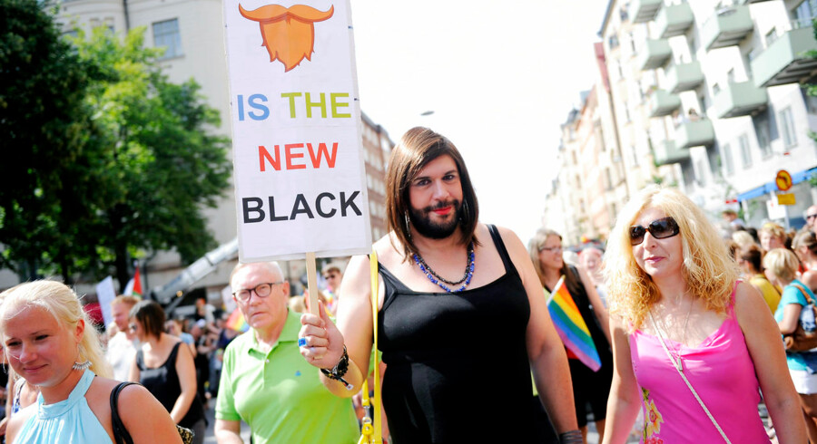 """A man dressed as Austrian Eurovision Song Contest 2014 winner Conchita Wurst holds up a sign that reads, """"Beard is the new black"""", at the annual gay pride parade in Stockholm August 2, 2014. REUTERS/Annika Af Klercker/TT News Agency (SWEDEN - Tags: TPX IMAGES OF THE DAY SOCIETY) ATTENTION EDITORS - SWEDEN OUT.NO COMMERCIAL OR EDITORIAL SALES IN SWEDEN. THIS IMAGE HAS BEEN SUPPLIED BY A THIRD PARTY. IT IS DISTRIBUTED, EXACTLY AS RECEIVED BY REUTERS, AS A SERVICE TO CLIENTS.NO COMMERCIAL SALES"""