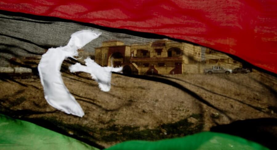 Libyens tredelte flag fra før Gaddafis magtovertagelse er blevet et symbol for oprørerne. Her flagrer det foran en politistation i Tobruk.