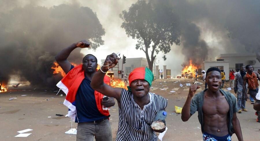 TOPSHOTS Demonstranter har torsdag været på barrikaderne i Burkina Faso, her råber de slagord foran brændende biler tæt på parlamentet i Ouagadougou.
