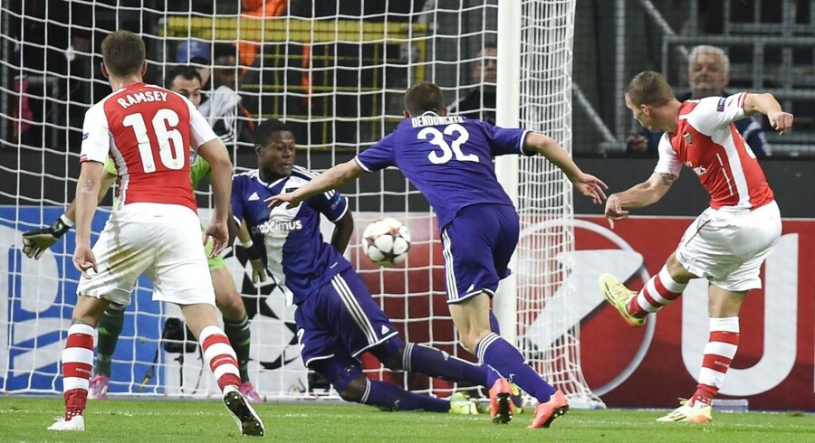 Arsenal's Polish-born German striker Lukas Podolski (R) shoots and scores during a UEFA Champions League group stage football match Anderlecht vs Arsenal at the Constant Vanden Stock stadium in Anderlecht on October 22, 2014. AFP PHOTO / JOHN THYS