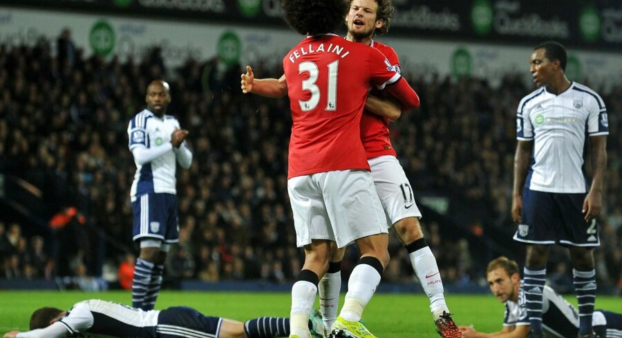 """Manchester United's Dutch midfielder Daley Blind (3rd R) celebrates scoring their second goal with United's first goal-scorer, Belgian midfielder Marouane Fellaini during the English Premier League football match between West Bromwich Albion and Manchester United at The Hawthorns in West Bromwich, central England on October 20, 2014. AFP PHOTO / PAUL ELLIS RESTRICTED TO EDITORIAL USE.No use with unauthorized audio, video, data, fixture lists, club/league logos or """"live"""" services. Online in-match use limited to 45 images, no video emulation.No use in betting, games or single club/league/player publications."""