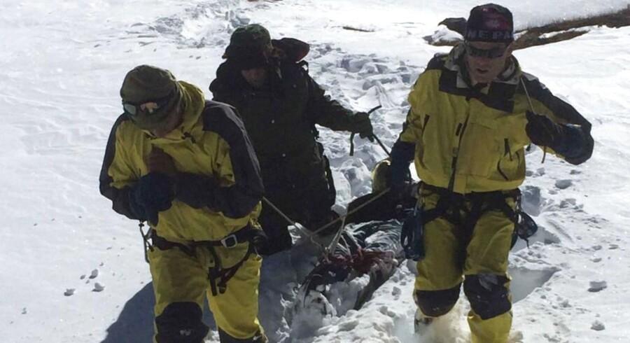 Bjærgningsmandskab fra den nepalesiske hær trækker ligene af turister, der omkom i den heftige snestorm, gennem sneen.
