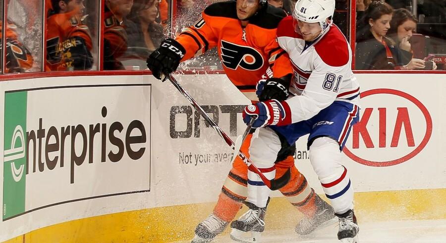 Montreal Canadiens' Lars Eller (nr. 81) tackler Vincent Lecavalier i banden i kampen natten til søndag i Philadelphia.