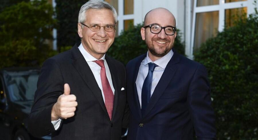 Medstifter Kris Peeters (venstre) og premierminister Charles Michel efter endeligt at have forhandlet en regering på plads i Belgien. Belgierne stemte om en ny regeringen den 25. maj.