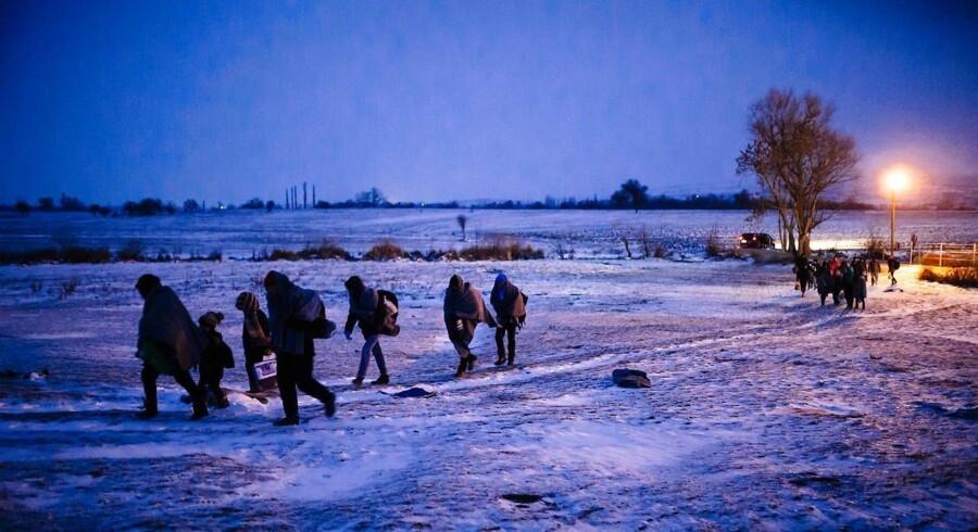 Migranter og flygtninge på en sneklædt mark ved den makedonske grænse til Serbien.