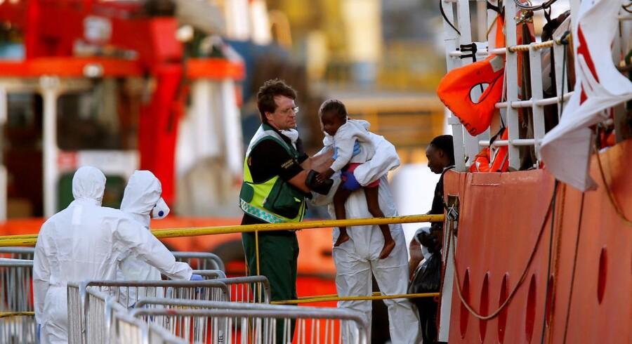 Et barn bliver båret fra et skib med migranter, som er anløbet til havnen i Valletta på Malta.