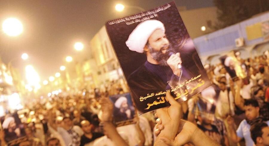 ARKIVFOTO: En demonstrant holder et billede af sheikh Nimr al-Nimr under en protest mod, at sheikhen blev arresteret i 2012.