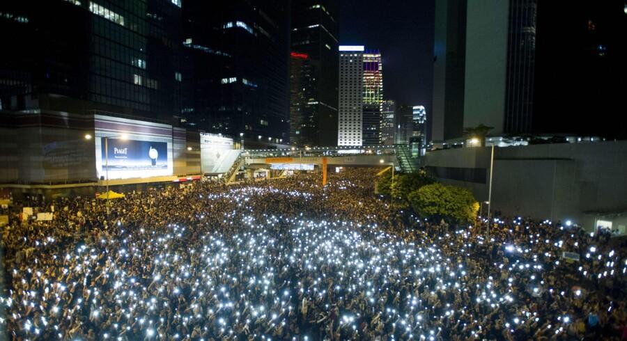Demonstranter, som for en stor dels vedkommende er studerende, brugte i aftes i Hong Kong deres mobiltelefoner for at billedliggøre deres indbyrdes solidaritet i protest mod det kinesiske styre i Beijing. De kinesiske myndigheder er overraskede over protesternes omfang. Foto: Xaume Olleros/AFP