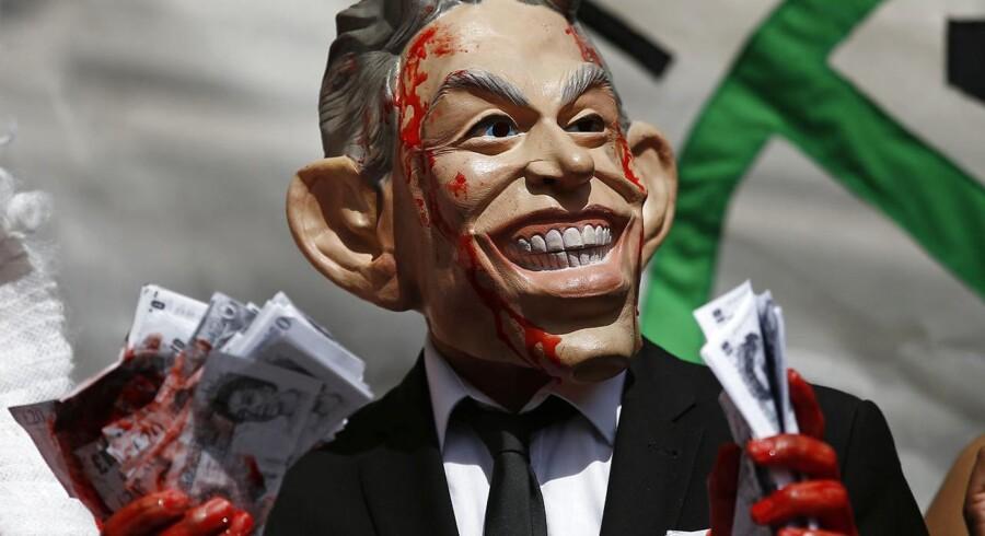 En demonstrant i London med en Tony Blair-maske med et bundt falske penge, indsmurt i teaterblod. Anledningen er offentliggørelsen af den længe ventede britiske Irak-rapport, som Sir John Chilcot står bag. REUTERS/Peter Nicholls